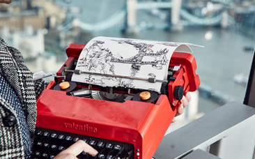 Keira Rathbone typewriter artist typing from life Tower Bridge from the Sky Garden Tower bridge on page and in background finger on key red Olivetti Valentine