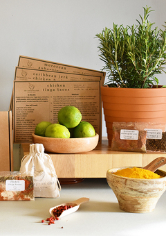 Fresh, potted thyme and recipe cards sit on a shelf, with spice packets, a bowl filled with turmeric, and limes in a dish in the foreground