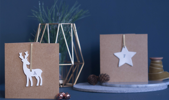 Two Christmas cards with reindeer and stars, ribbon, copper bells and gold ornament