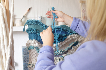 Lucy Rowan weaving a large blue weaving on a wooden loom