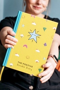 The yellow and turquoise Positive Doodle Diary being held towards the camera