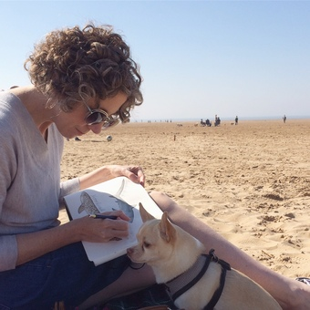 Dani Williams on the local beach with sketchbook and Riley chihuahua.