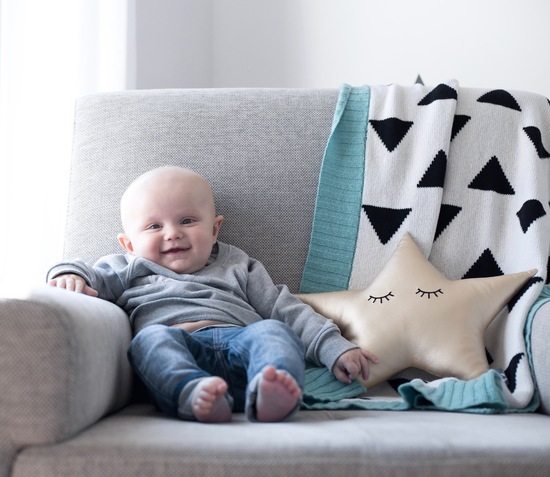 Baby with blanket and cushion