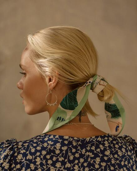 woman wearing a pistachio green thin silk scarf in her hair
