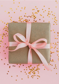 Small gift box wrapped in kraft paper with a pink ribbon on gold glitter