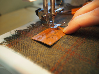 Sewing one of our personalised leather patches onto a scarf