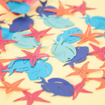 Under the Sea themed paper table confetti with fish and starfish