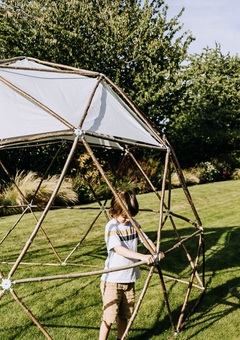 A young boy helps to build the geodesic garden pod