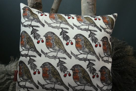 A square linen cushion with a print of Robin birds with red berries. The cushion sits on a wooden chair against a dark grey background..