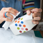 Hanne Rysgaard hand applying polka dot transfers to a milk jug