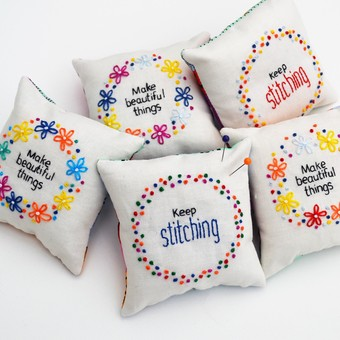 a stack of hand embroidered pincushions with the words 'make beautiful things'