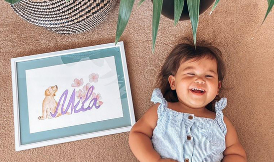 Happy Mila laying with her personalised made to order name art.