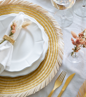 Gold woven natural straw placemat in an elegantly decorated dinner table