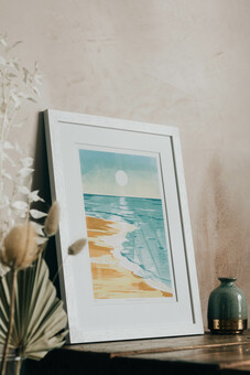 Framed print of a beach seascape at sunrise leaning against a wall.