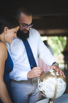 Wedding guests signing gold guestbook globe