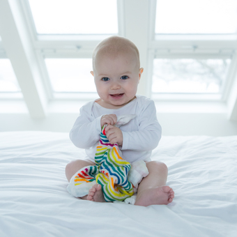 Smiley baby with a Rainbow Star Comforter