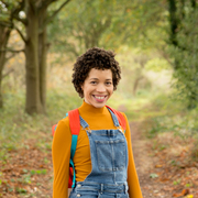 Lady of mixed heritage is smiling into the camera. She has a short afro and wears denim dungarees, a mustard roll neck jumper and a red backpack.