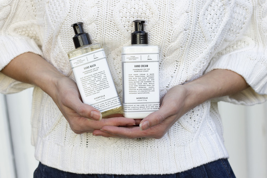 Bella, our founder, holding our hand wash and hand cream.
