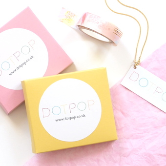 A photo of some of our colourful packaging. A yellow and pink box with a DOTPOP sticker and a small business card.