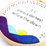 a hand embroidered sunrise with the text 'It's always darkest before the dawn'