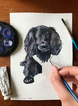 Illustrator, Gaby, working on a painting of a black dog