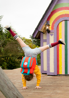 Image of a young girl doing a handstand in front of a rainbow striped playhouse. The girl is wearing a magnetic red dinki backpack & red biggi pouch attached.