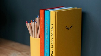 The yellow Positive Planner, blue Positive Bullet Diary and orange Positive Wellness Journal standing together on a shelf next to a pot of colouring pencils