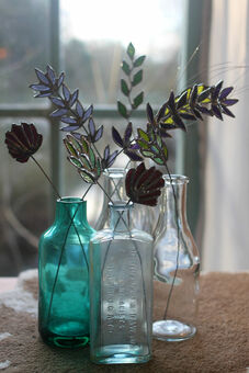 Selection of wildflowers and grasses displayed in glass bottles