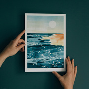 Hands holding a print of a beach scene at golden hour with a dark green wall behind. The print has gold leaf details.