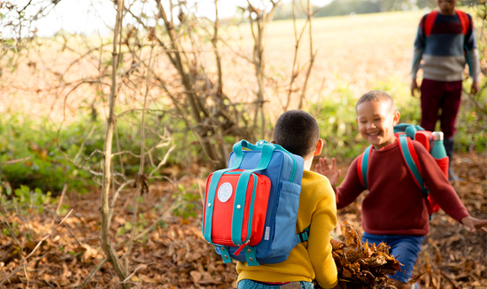 Two brothers running towards each other smiling. They wear brightly coloured backpacks with magnetic pouches attached.