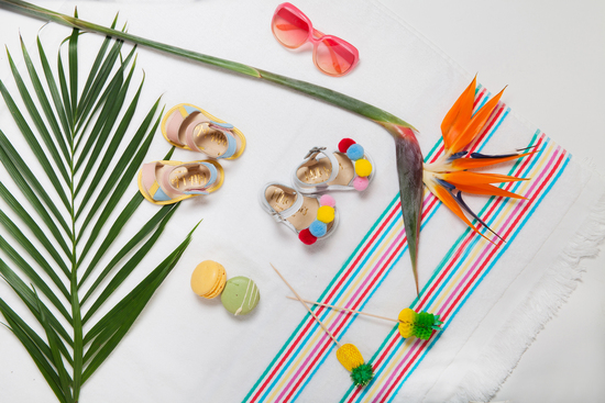 Baby sandals flat lay with tropical plants and macaroons