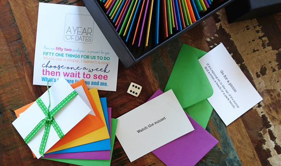 The contents of A Box of Dates showing example cards, the dice and coloured envelopes