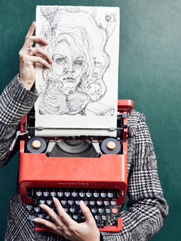 Keira Rathbone Typewriter ARtist portrait with typewriter and self portrait typewriter art work in front of face, fingers on keys and holding paper