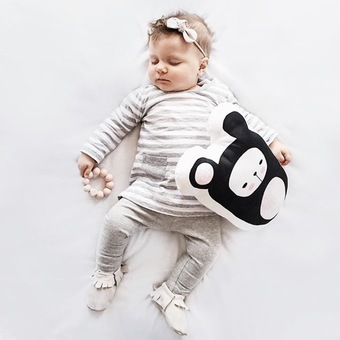 Sleeping baby dressed in grey and white lying on back holding a handmade Brunta Bear cushion