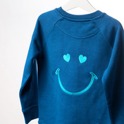 The LOVE sweatshirt features a beautifully embroidered smile and heart eyes on the reverse paired with the simplicity of Love in vibrant text on the front