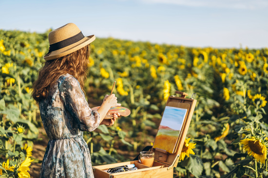 Lady in a sunflower field wearing a hat, painting on an easel with watercolours