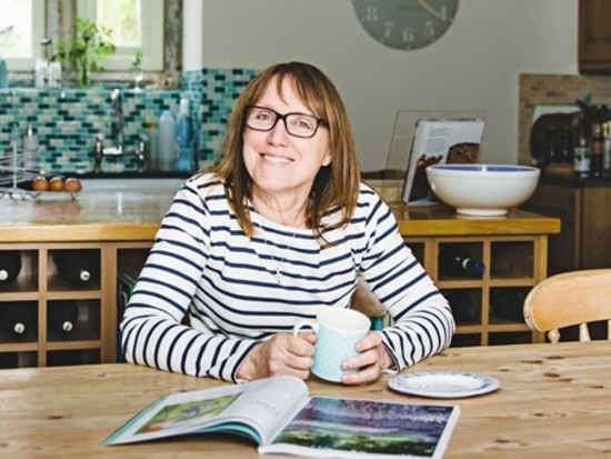 A picture of me (Jane) in my kitchen at Wadsley Hall Farm, sat at the kitchen table with a cuppa and a magazine!