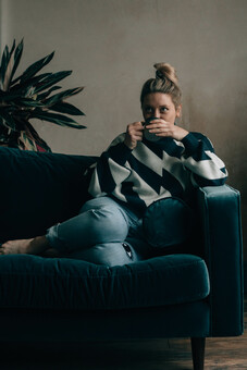 Founder of Slow Sunday, Liz, sat on a blue velvet sofa drinking a cup of tea.