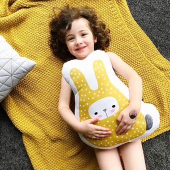 Aerial view of young girl lying on a yellow blanket and holding a handmade yellow Gerta bunny cushion by Hesperoo