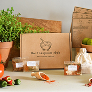 A Teaspoon Club box is front and centre with spice packets displayed around it, as well as fresh chillies and oregano