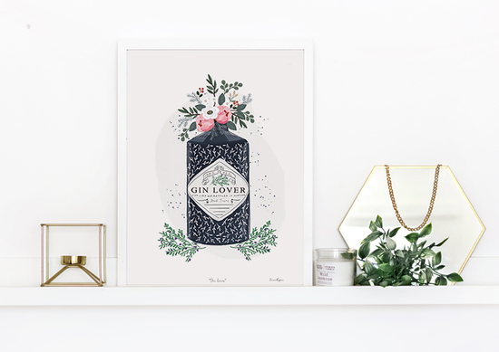 A framed gin and flowers bestselling print on a shelf by Emma Bryan Design