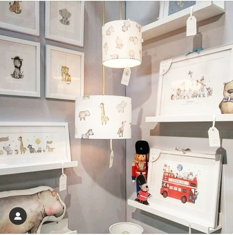 Children's luxury nursery interior designs displayed on a wall including kid's framed wall art prints of a london bus and safari animal lampshades