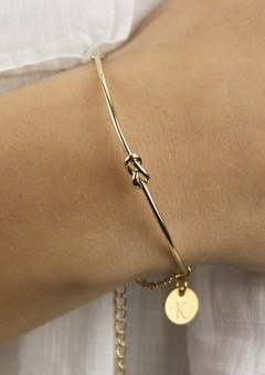 A modern delicate knot bangle, personalised with an engraved disc