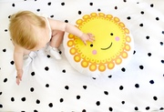 Aerial view of baby sitting up and reaching out to a yellow Marigold cushion handmade by Hesperoo