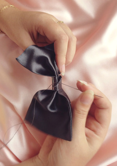 close up of hand sewn finishing a dark grey silk hair bow
