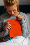 A blonde lady sat in bed wearing grey pyjamas and holding an orange Positive Wellness Journal