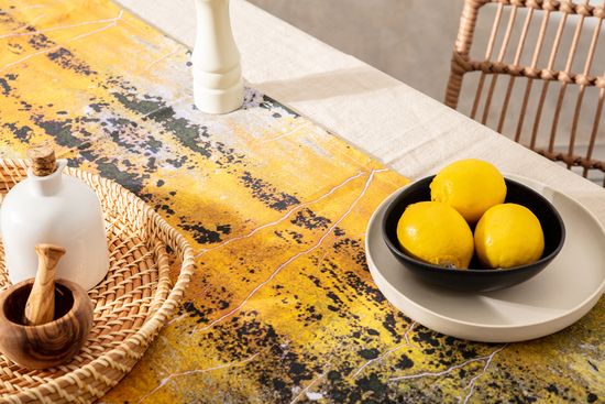 yellow and orange table runner, lemons in black bowl